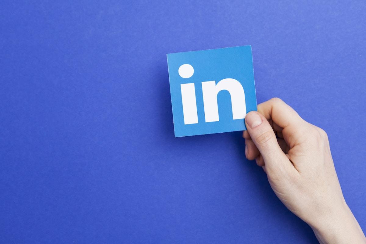 Logo Linkedin tenu en main